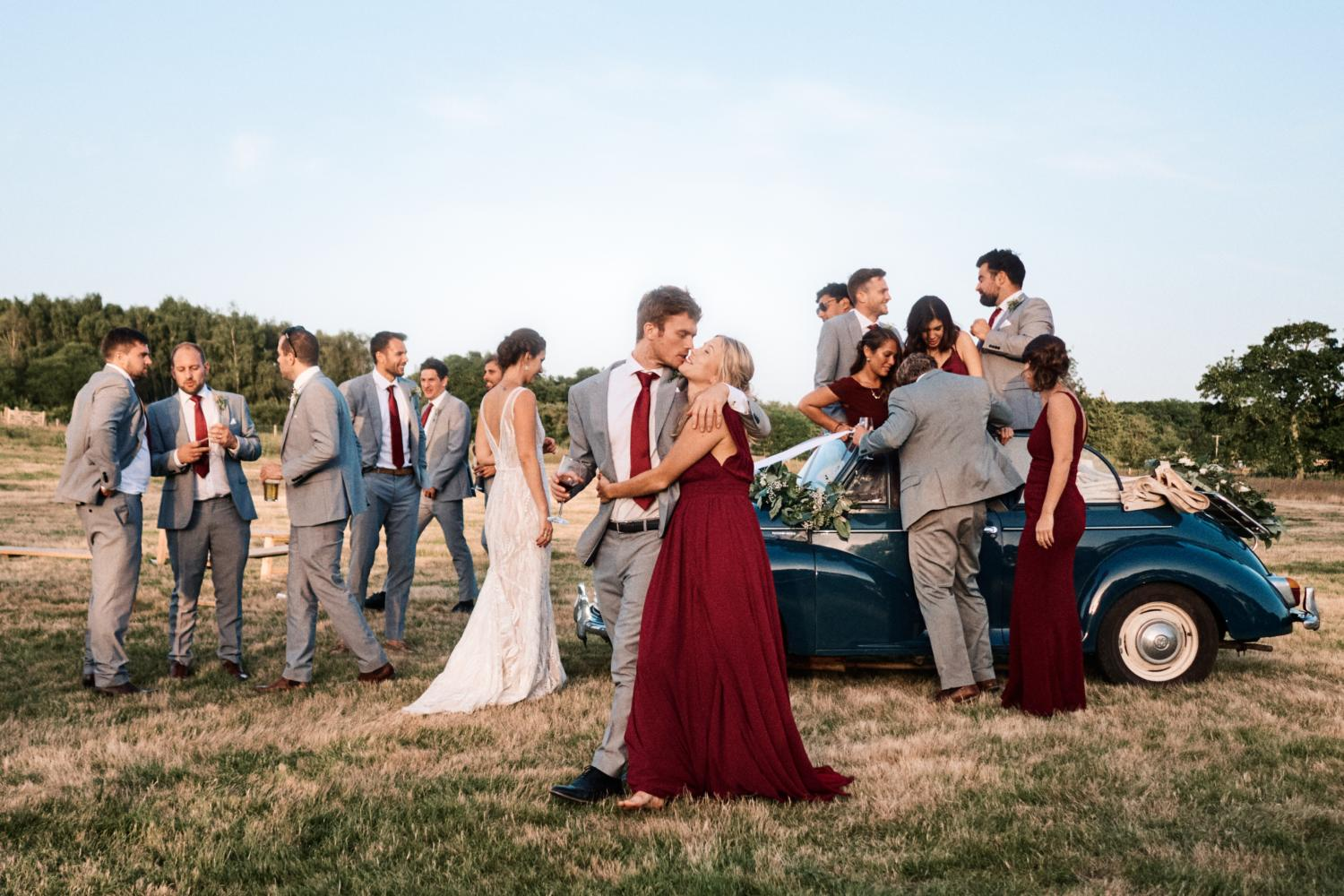 Bridal party climb out of convertible car in a field
