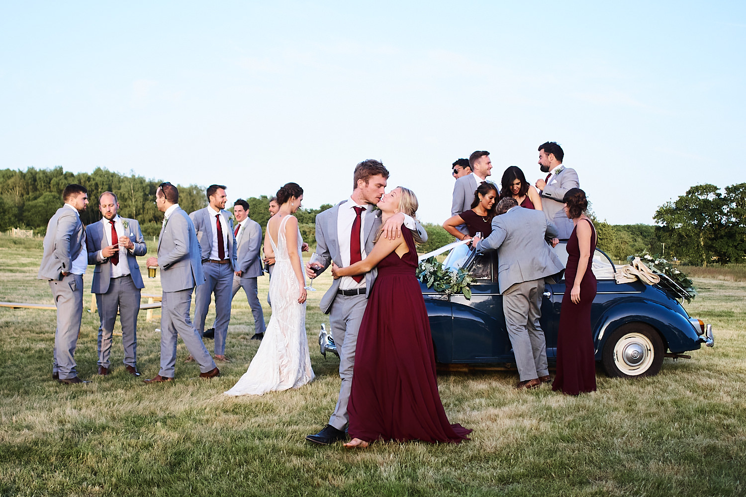 Bridal party climb out of convertible in a field