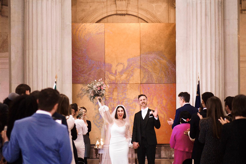 newly weds walk down the aisle at Dublin City Hall
