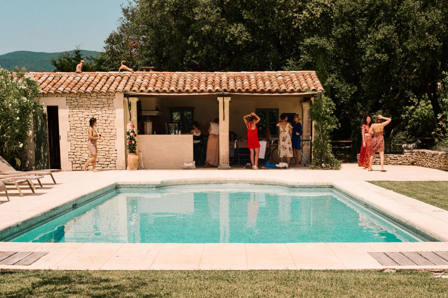 Bridal party get ready beside pool in France