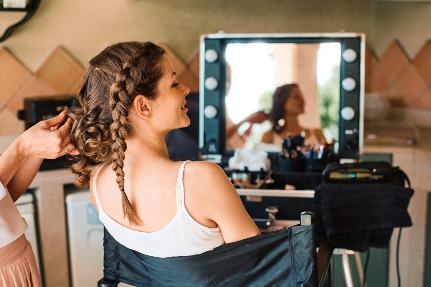 Bride gets her hair platted on wedding morning