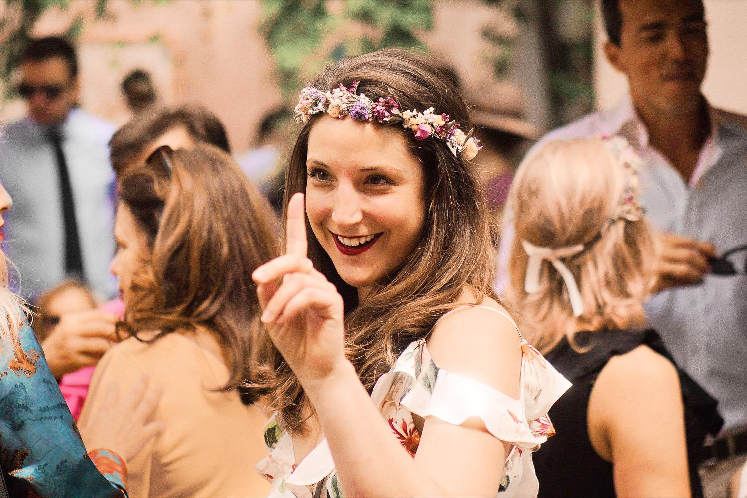 Bridesmaid with flowers in her hair, raises her finger