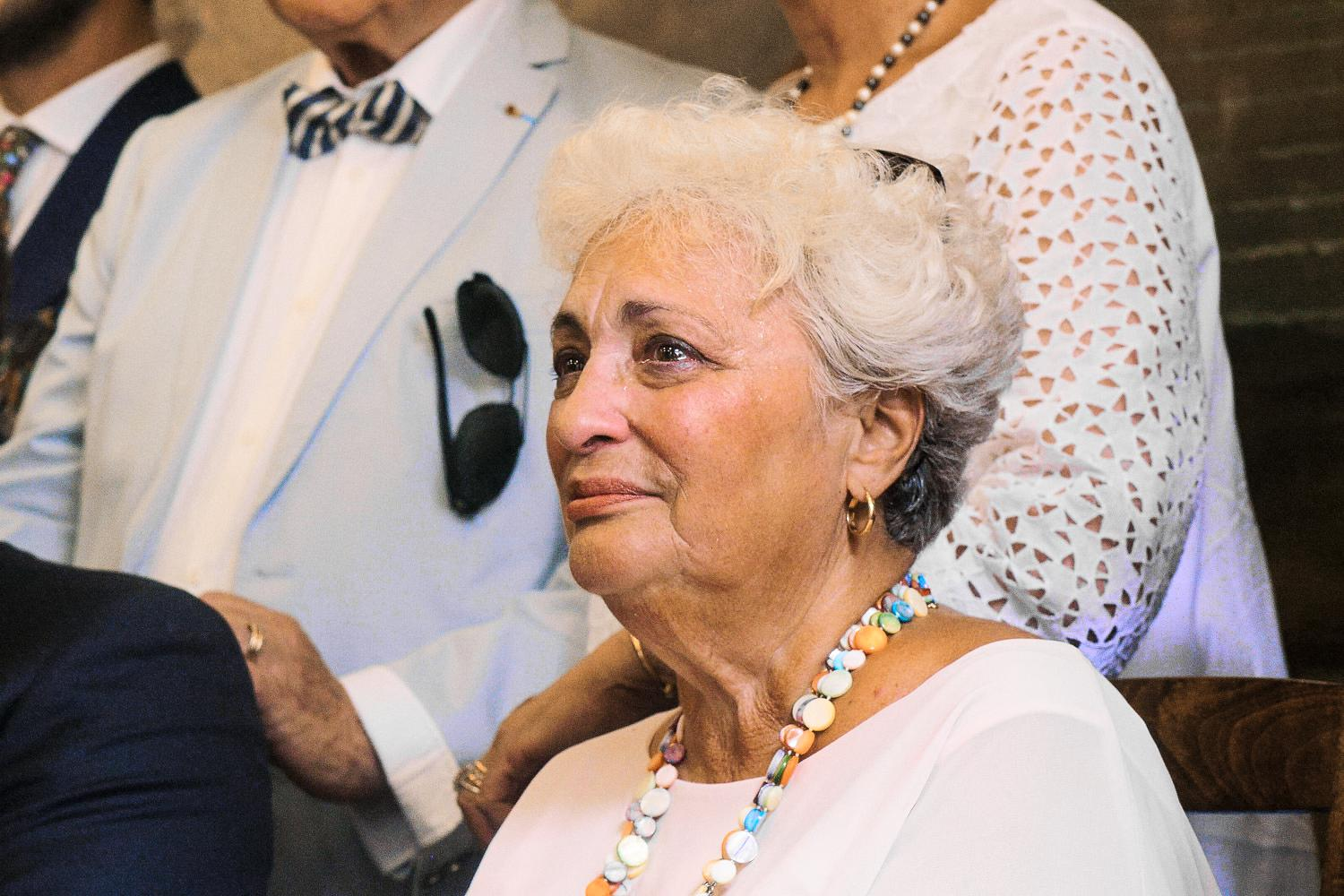 Emotional mother of the groom sheds a tear during wedding ceremony