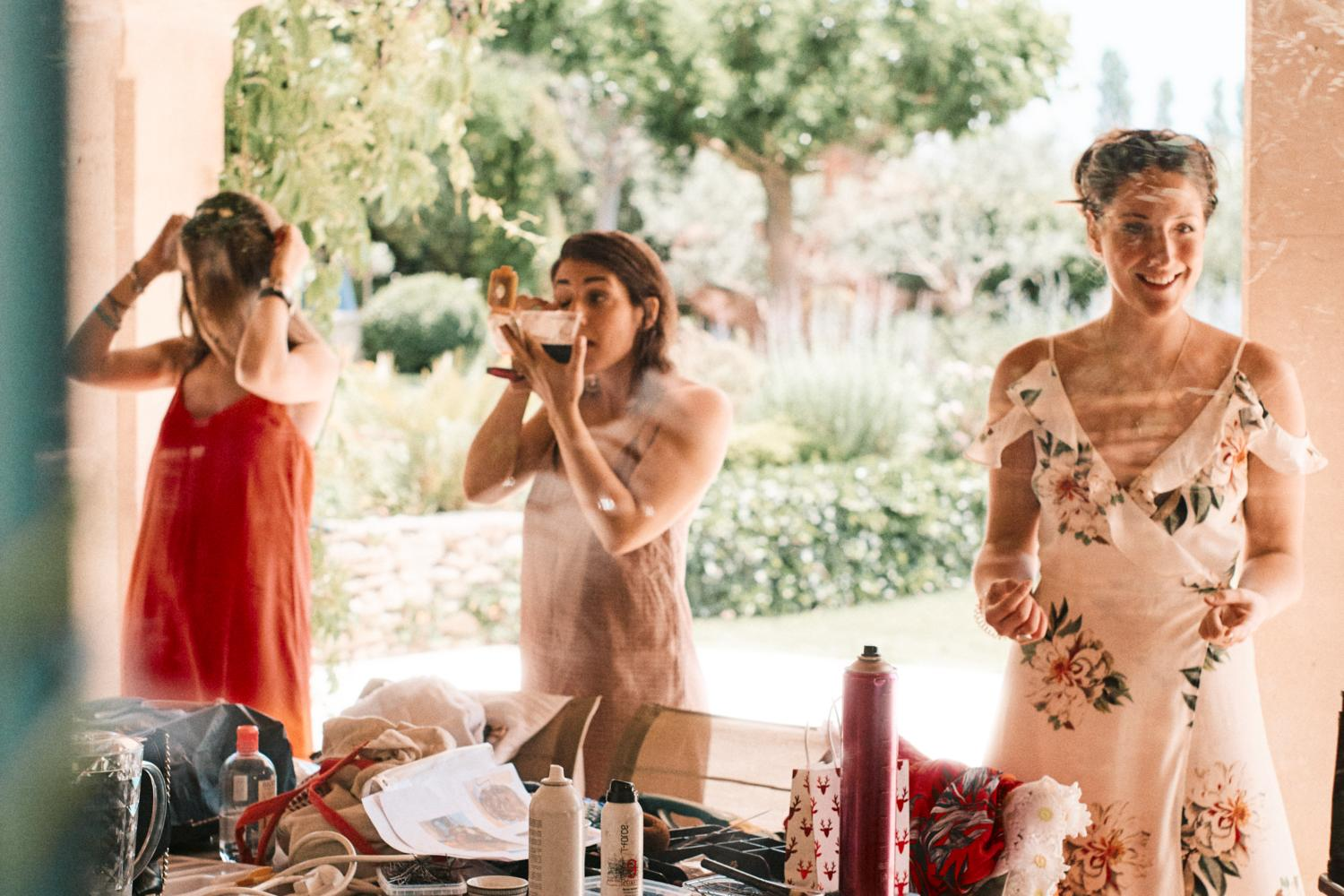 Three bridesmaids apply their own makeup outside in the sun