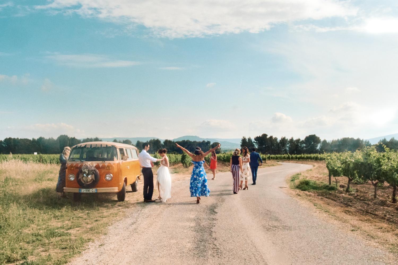 A bridal party exit an orange VW camper van
