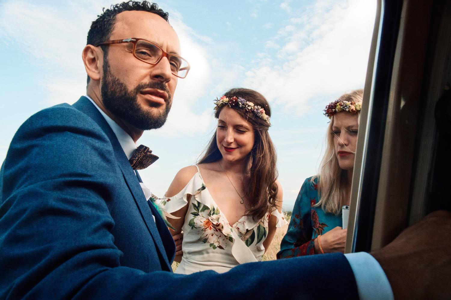 A groom wearing glasses exits van with two bridesmaids