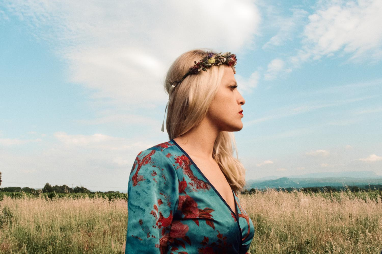 A bridesmaid with floral head piece looks pensively in a field in France