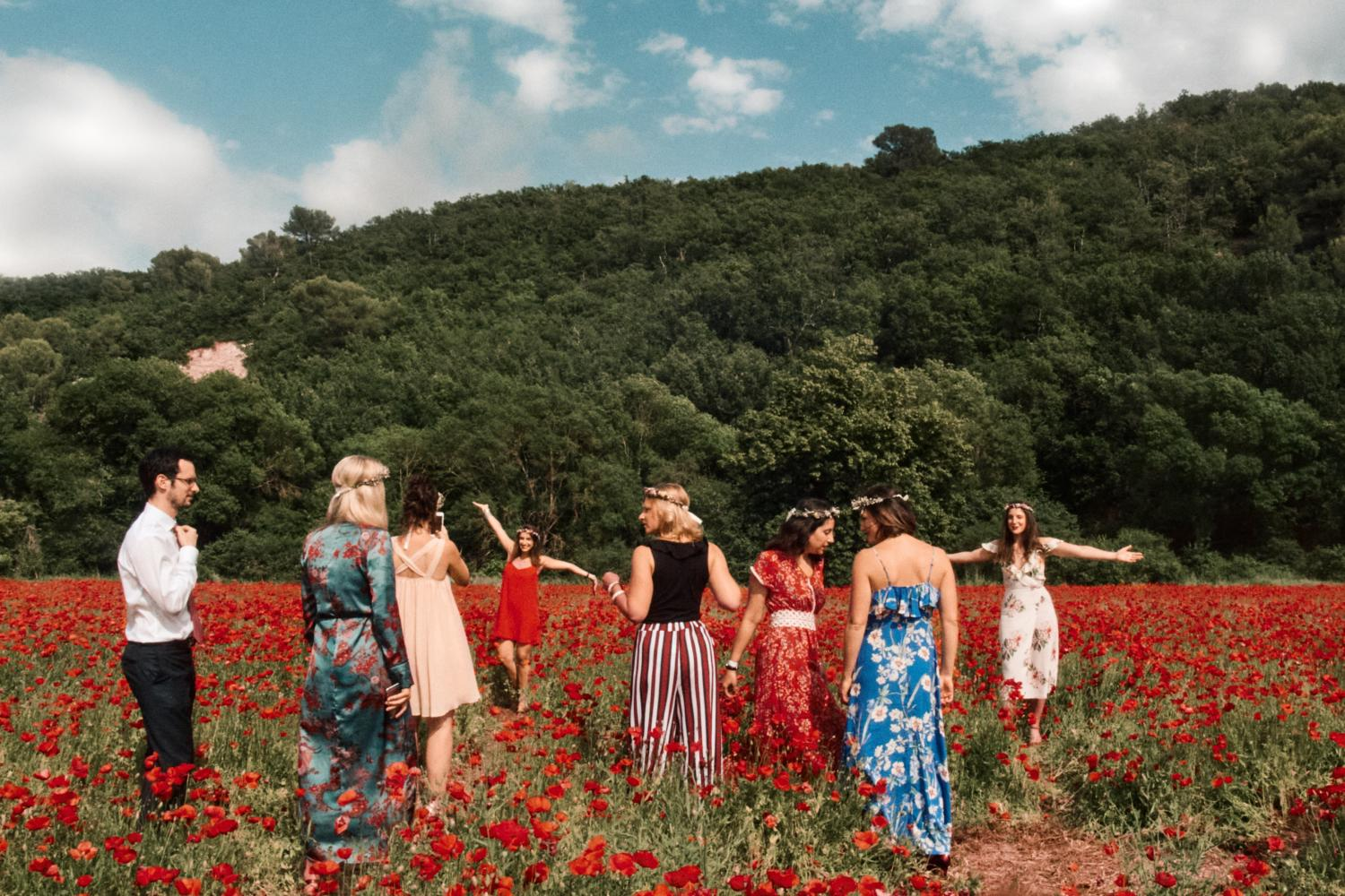 A bridal party explore a poppy field in France