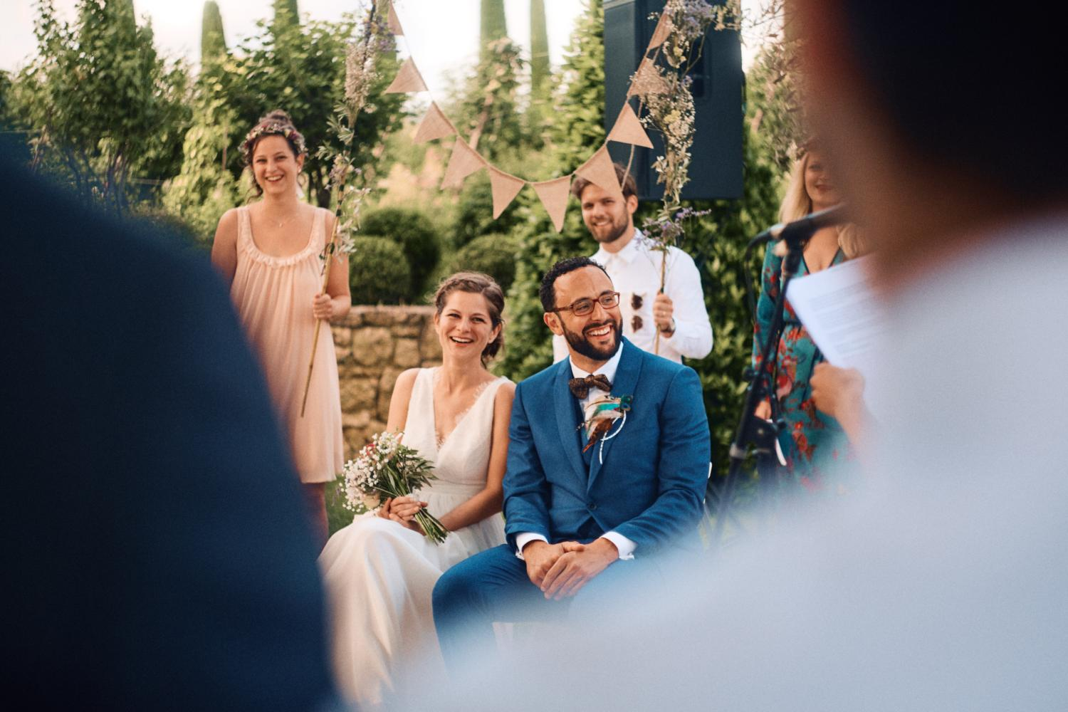 Wedding couple listen and laugh to speeches during outdoor ceremony at Chateau Val Joanis