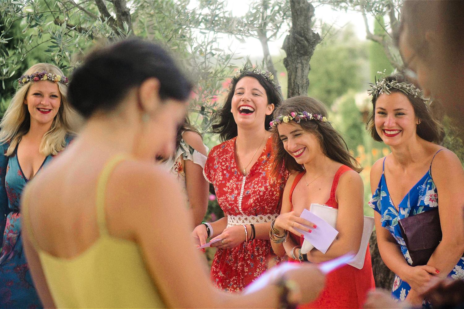 Bridal party laugh during outdoor speeches