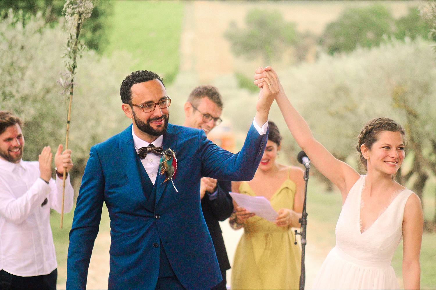 Wedded couple raise their hands in celebration during outdoor wedding ceremony