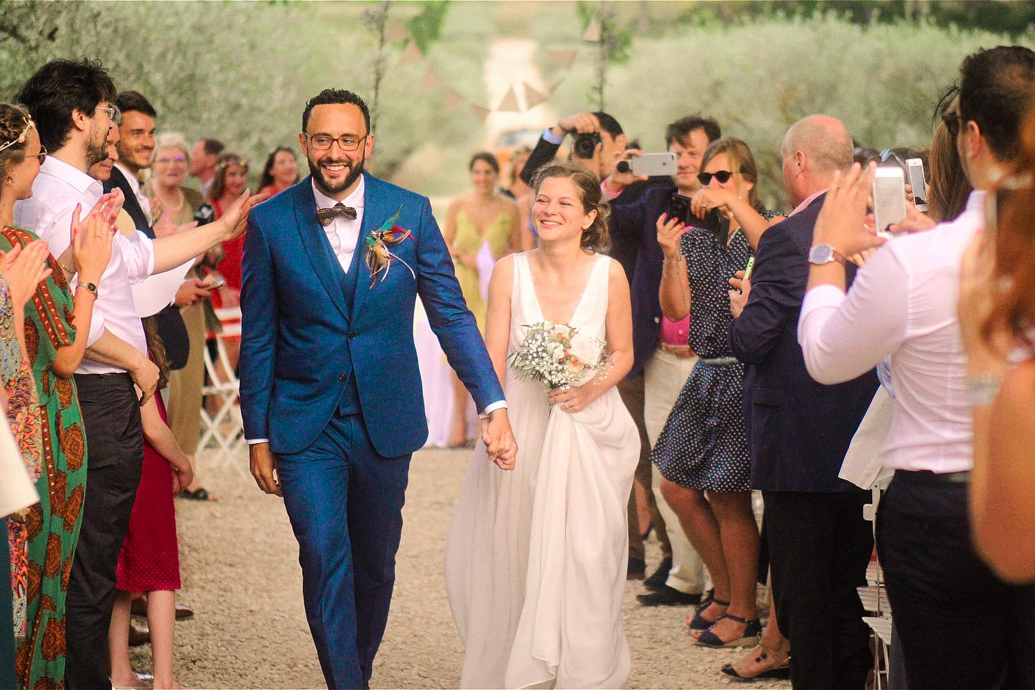 Married couple walk down the aisle at Chateau Val Joanis