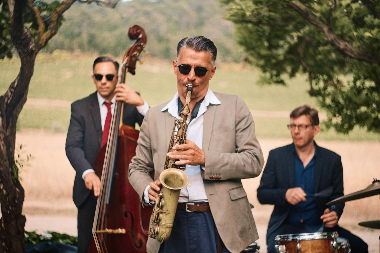 A saxophone player performs outdoors with band at Chateau Val Joanis