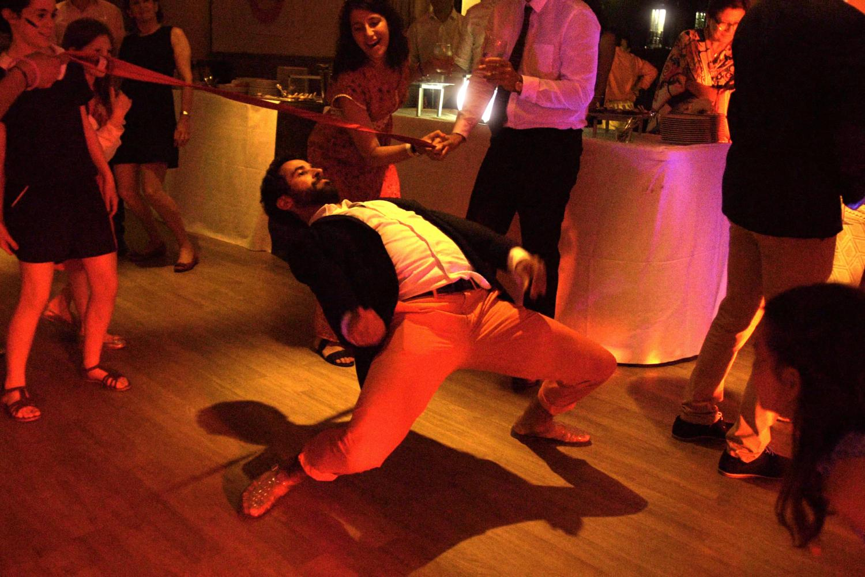 Man plays limbo at wedding