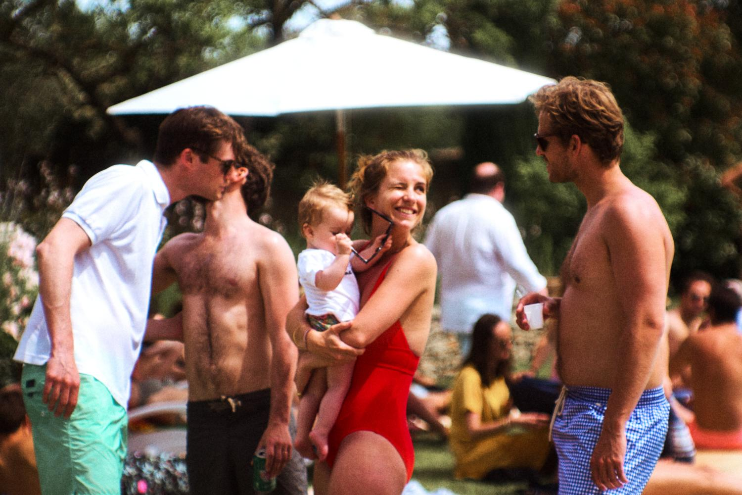 Wedding guests greet each other at a pool party in France
