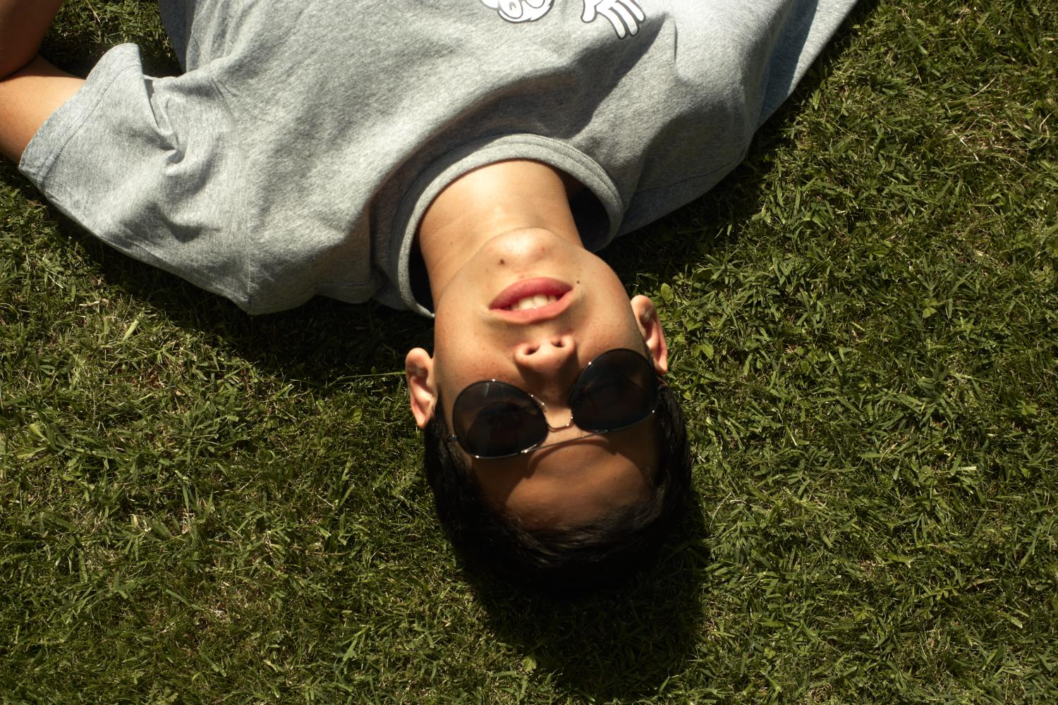 A person wearing sunglasses and lying on the grass