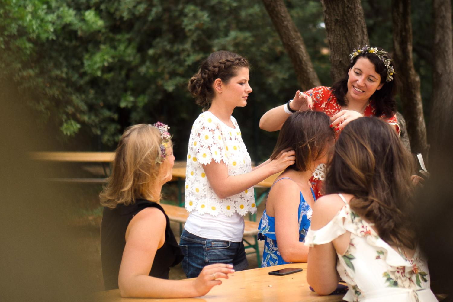 Bride in floral top does friend's hair on wedding morning