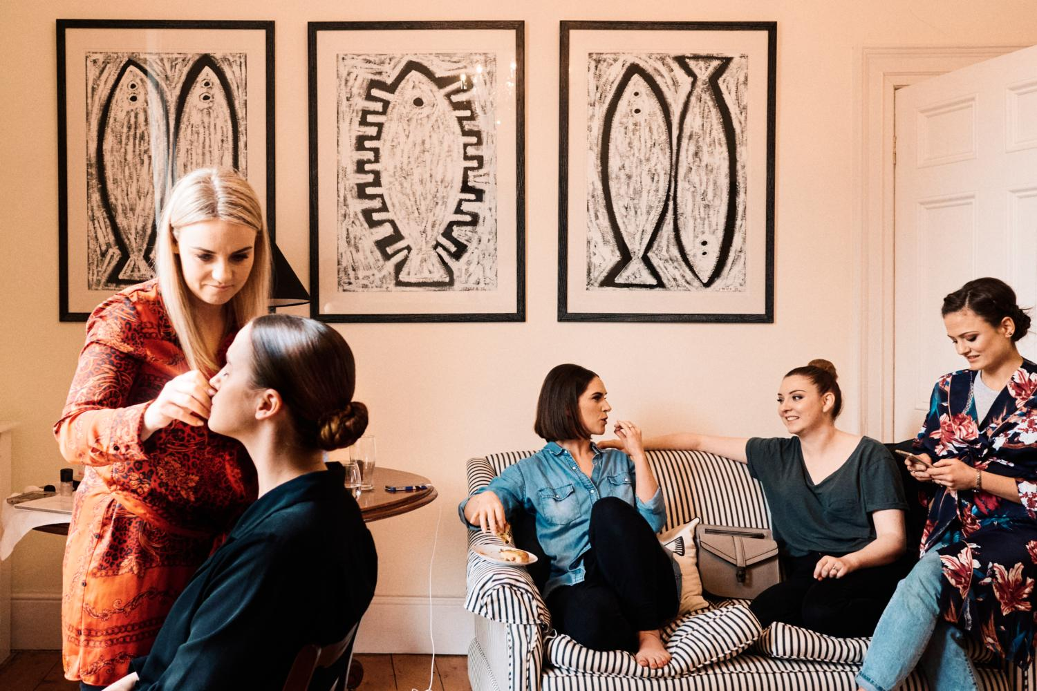 A bridal party relax during makeup in front of paintings of primordial fish