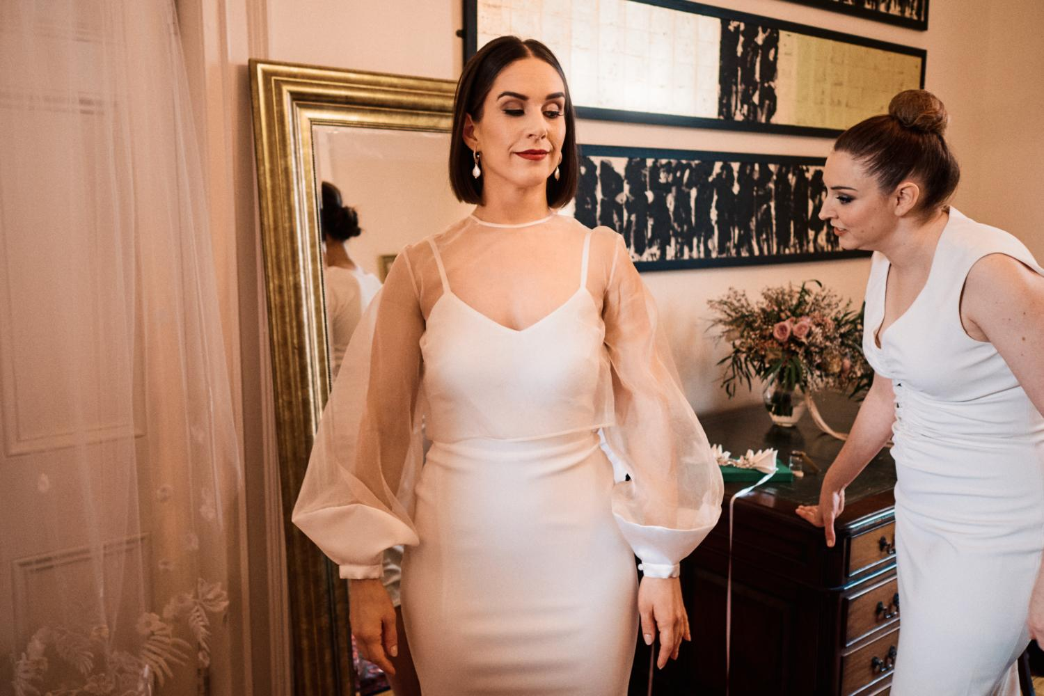 A bride tries on her dress in front of a mirror