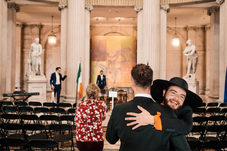A man in a hat hugs a groom inside Dublin City Hall