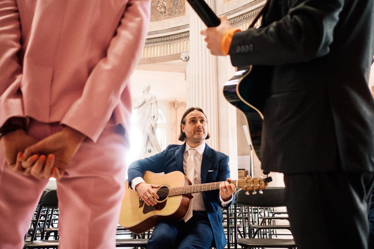 A groomsman practices acoustic guitar at Dublin City Hall