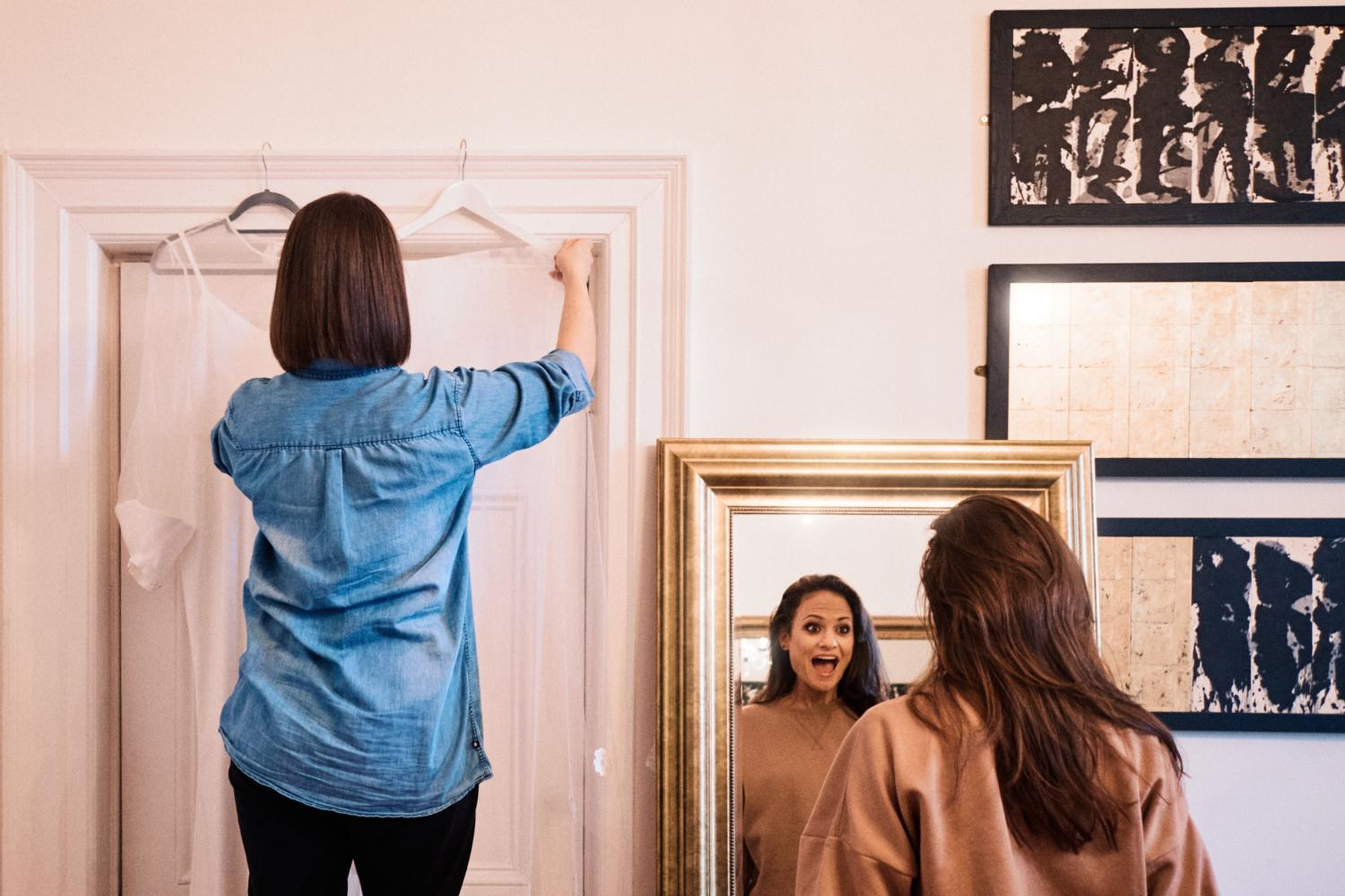 A bride in denim hangs up her veil while her friend smiles in the mirror