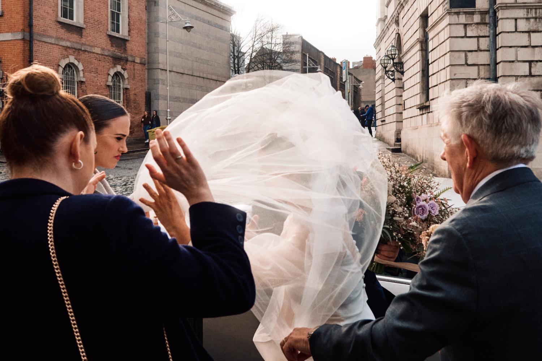 The wind blows a bride's veil outside Dublin City Hall