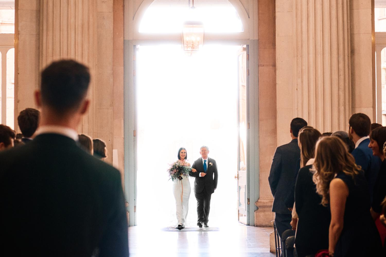 A bride walks up the aisle with her father at Dublin City Hall