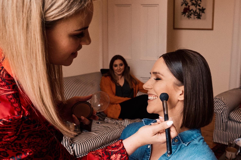A makeup artist applies blusher to the cheeks of a bride