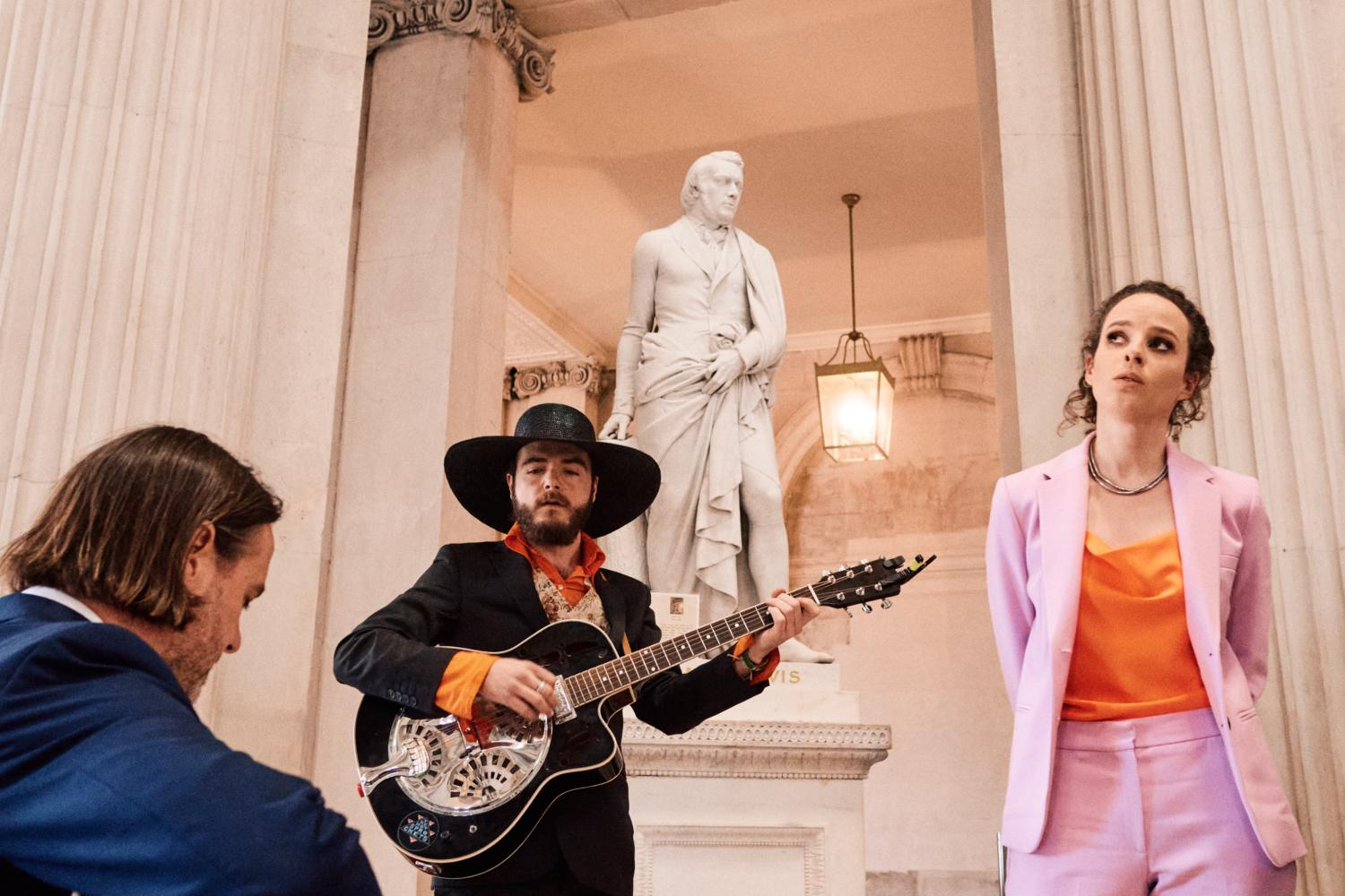 A woman in a pink suit sings with a guitarist in Dublin City Hall