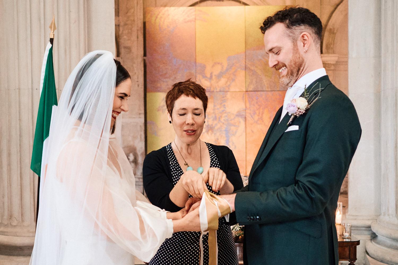 A bride and groom do a handfasting ceremony at Dublin City Hall