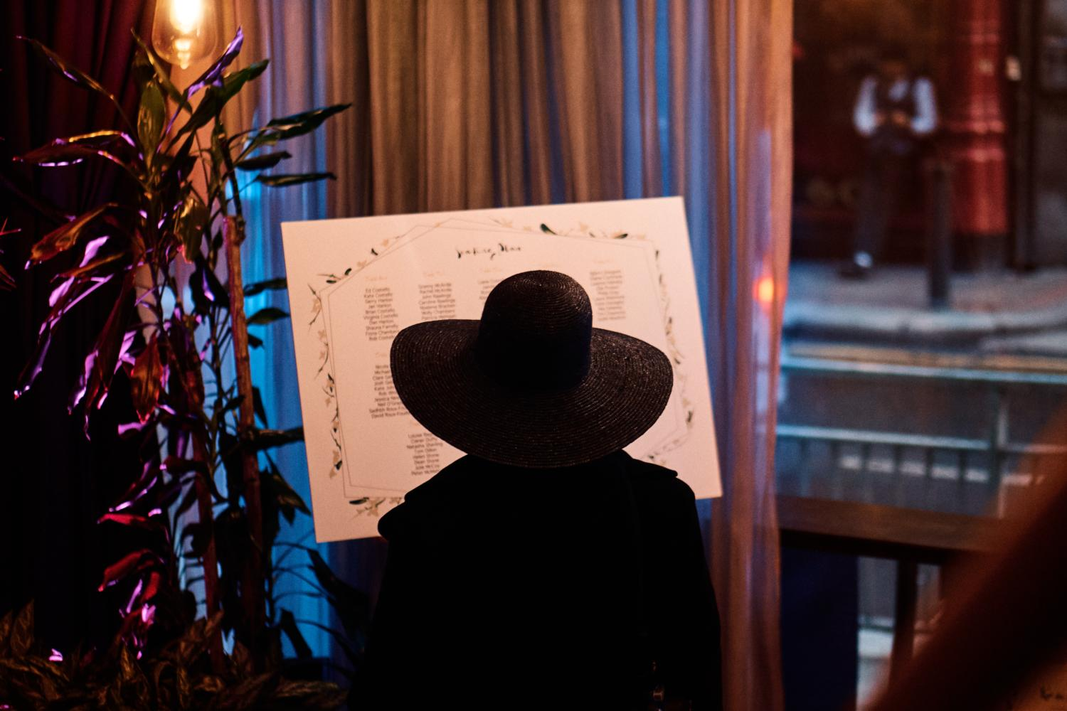 A man in a hat reads a wedding table plan at Medley, Dublin
