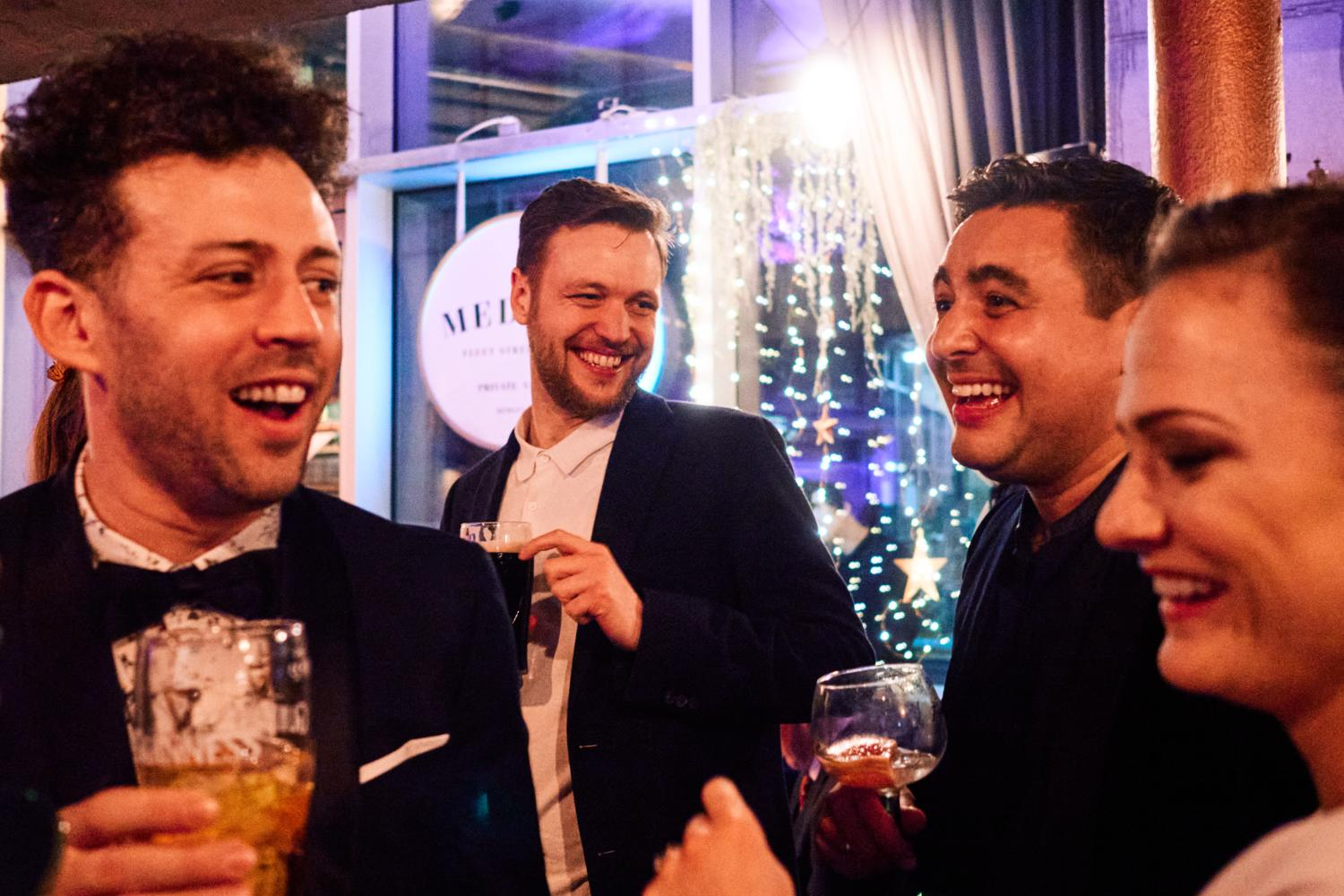 Four wedding guests laugh during a drinks reception at Medley, Dublin