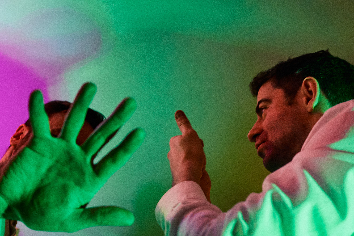 Two dancers make expressive hand gestures in green light