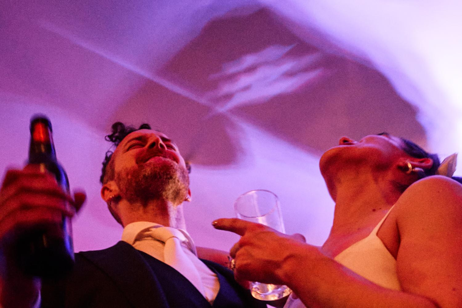 A bride and groom celebrate and dance with drinks