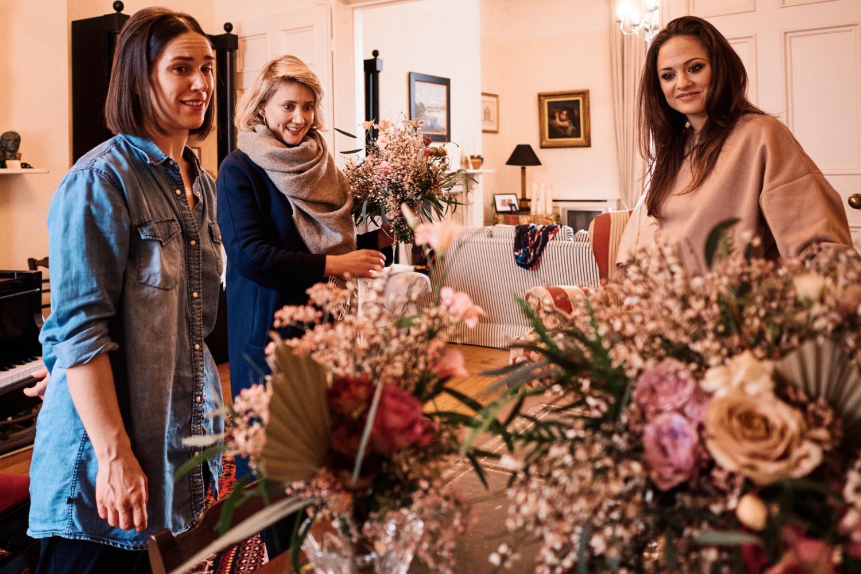 A florist delivers an arrangement of flowers to a bride's house
