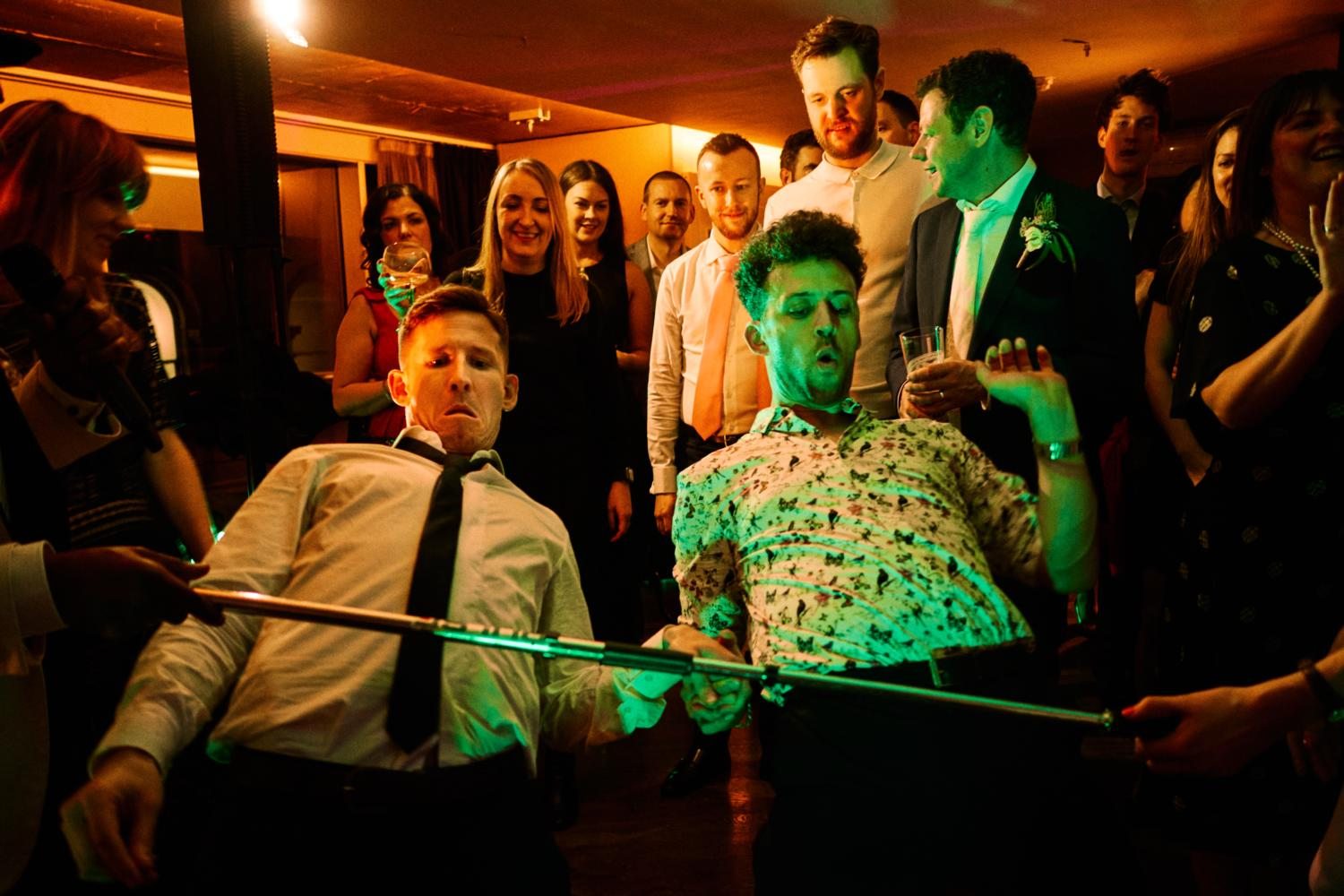 Two dancers play limbo at a wedding party in Dublin