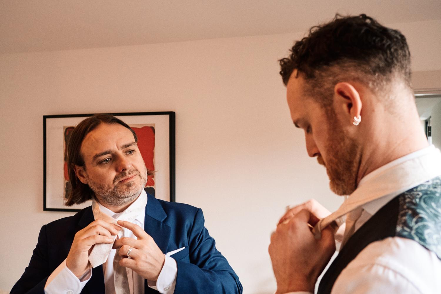 A groom and friend do their ties on a wedding morning