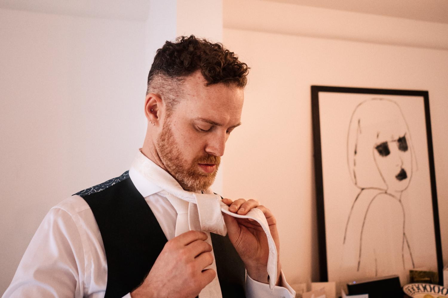 A groom in waistcoat fixes his white tie in front of a painting
