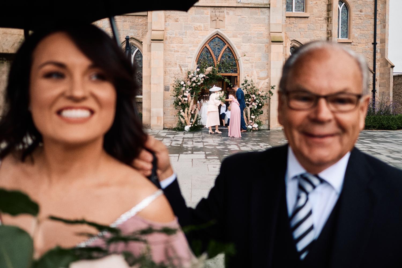 A driver holds an umbrella for a bridesmaid outside a church