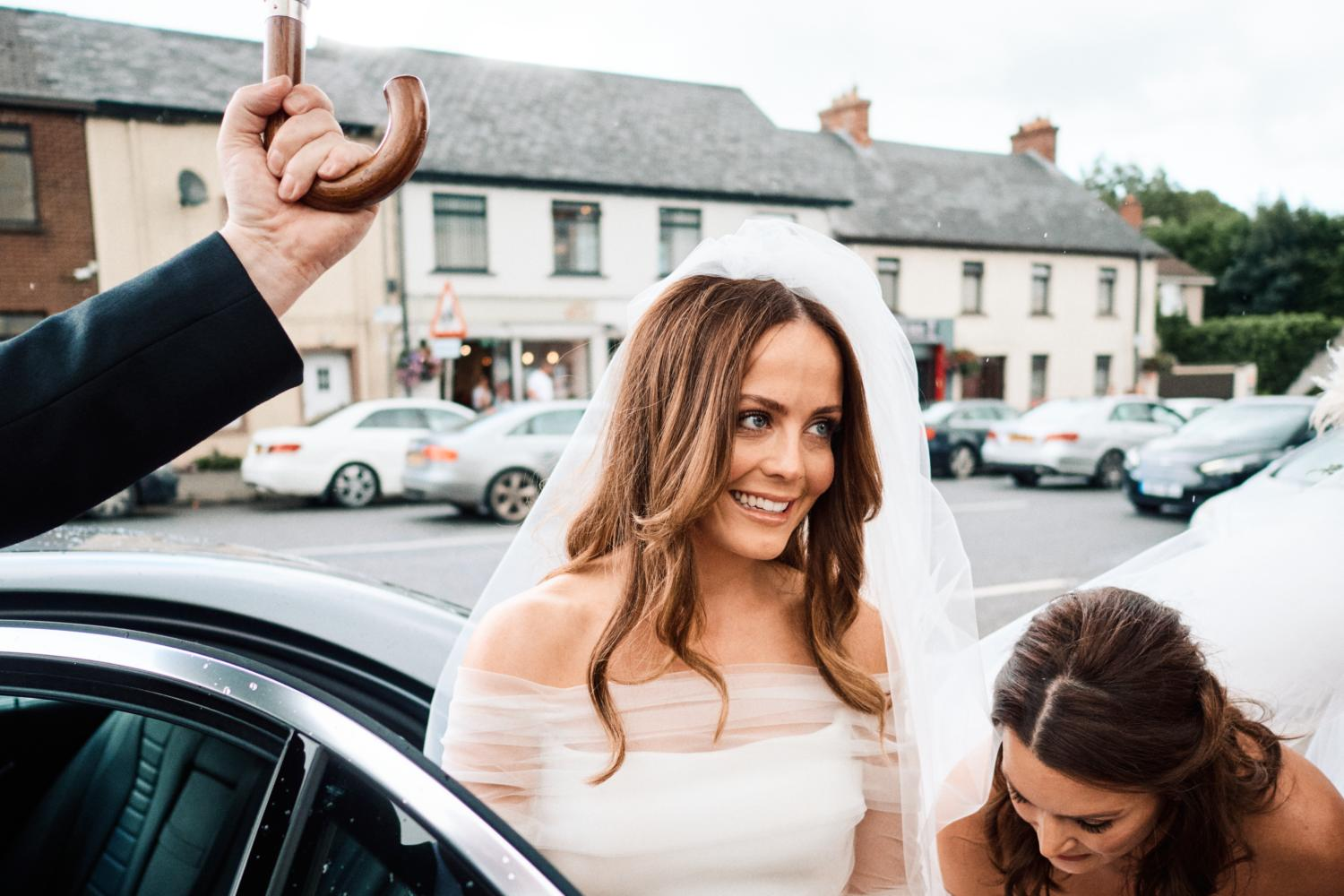 A driver holds an umbrella for a smiling bride in Dungannon