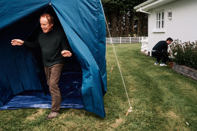 A man exits a blue tent in a garden
