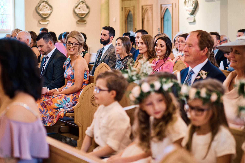 Wedding guests smiling at a Catholic wedding mass