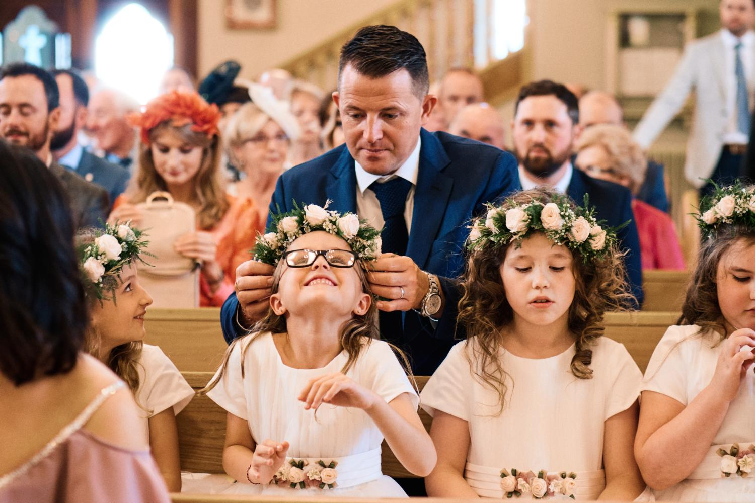 A father helps fix a child's floral head piece