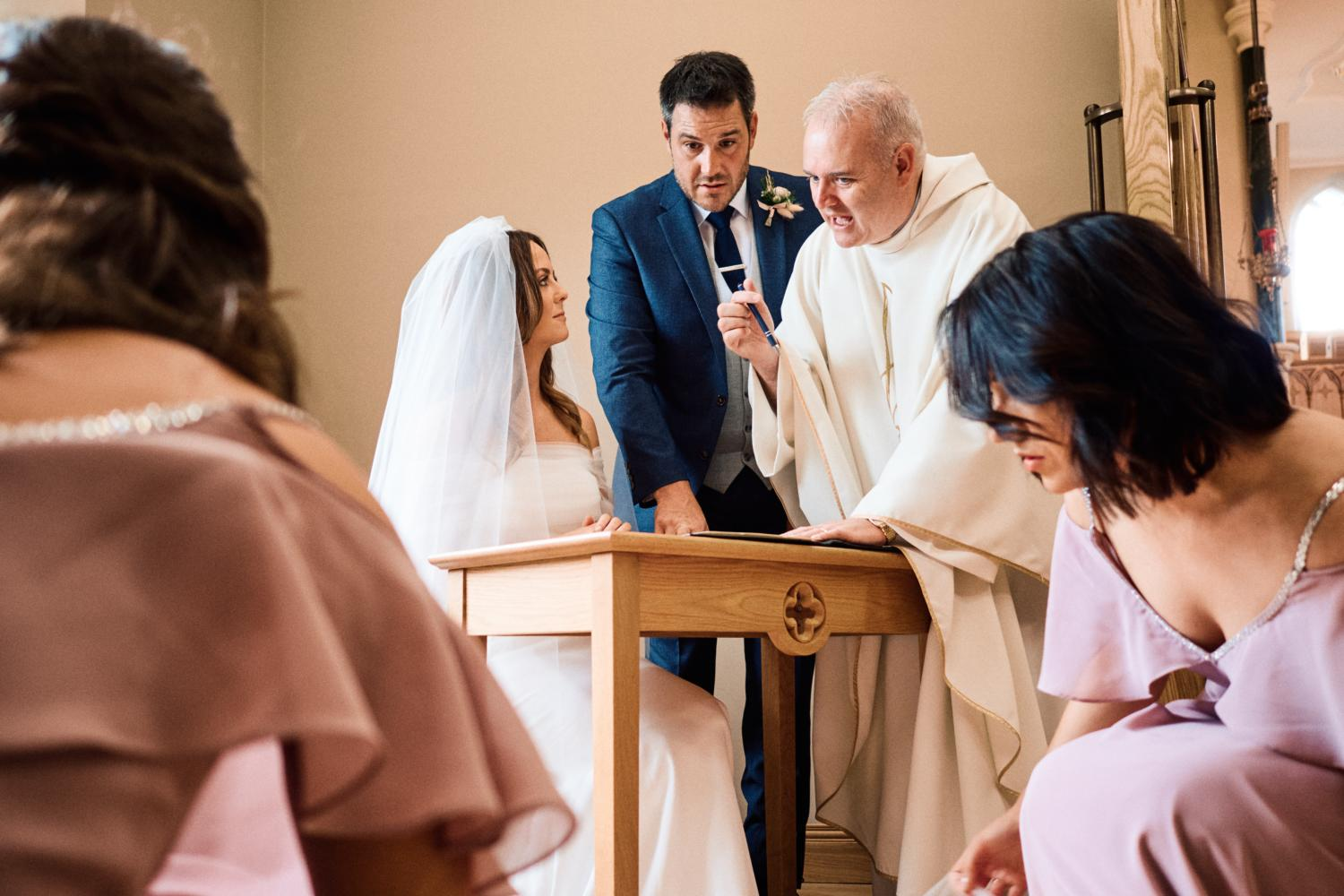 Bride and groom sign marriage certificate in the company of a priest