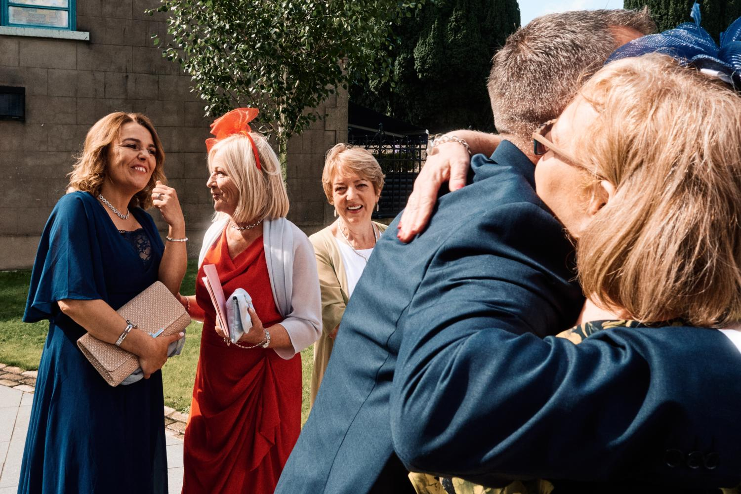 Wedding guests greet each other outside a chapel