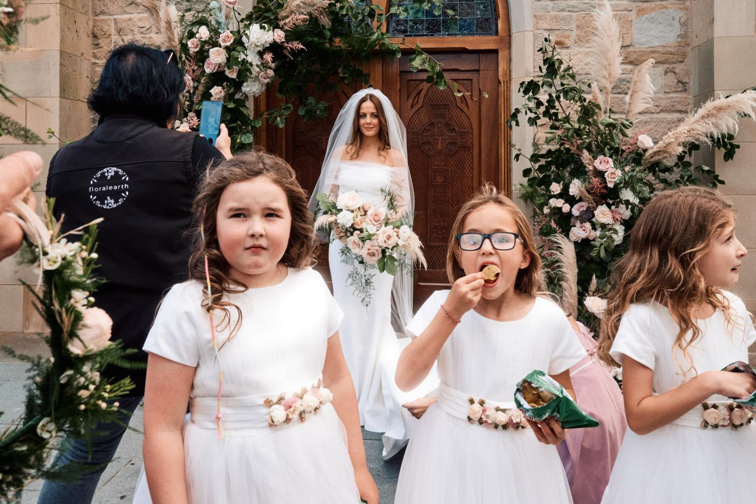 Flower girls eating crisps in front of a bride in Dungannon
