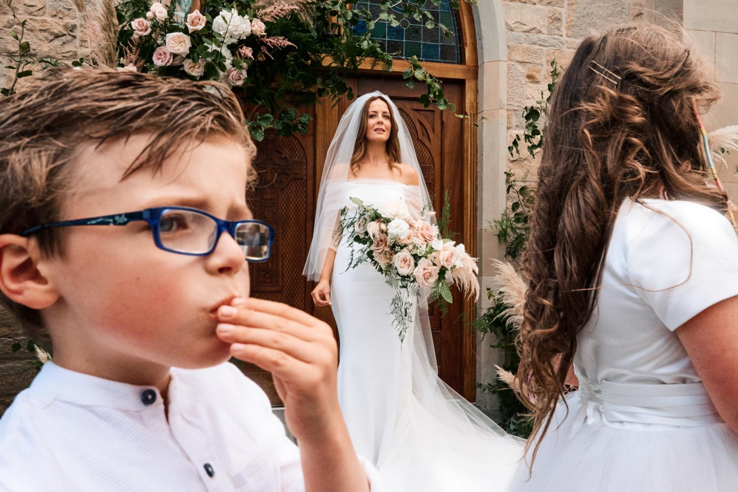 Children eating crisps in front of a bride outside a church