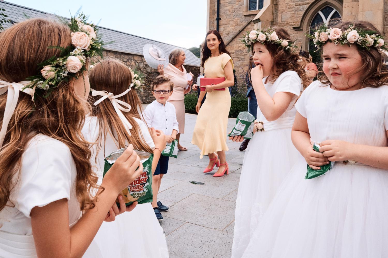 Flower girls eat crisps at a wedding