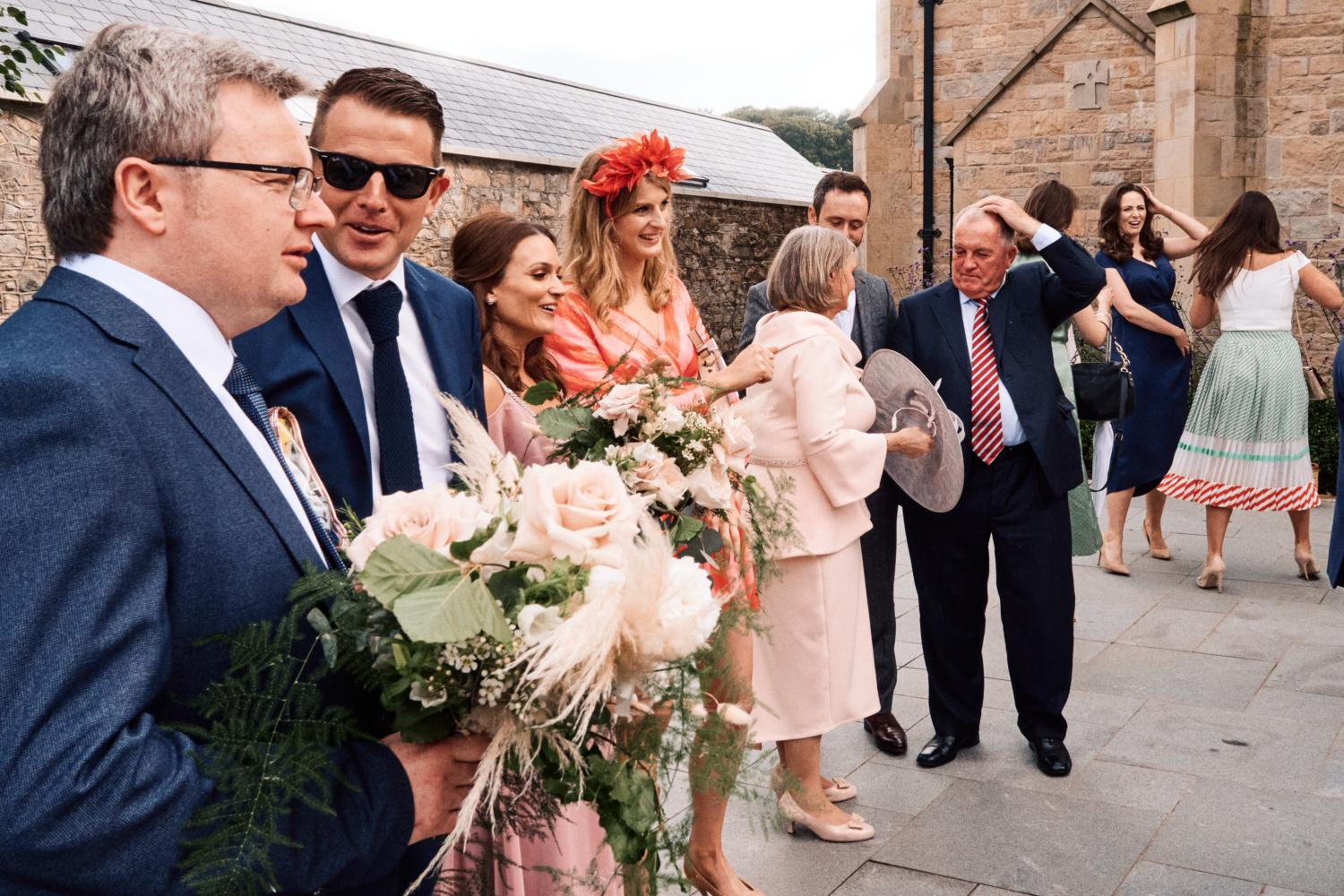 Wedding guests holding flowers outside a chapel
